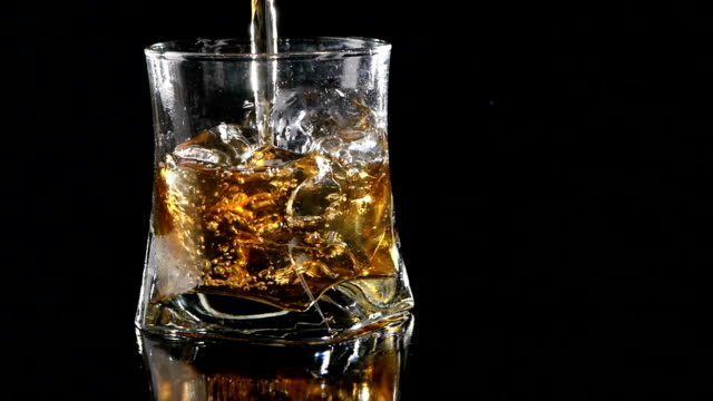Whiskey being poured into a glass against black background. Close video