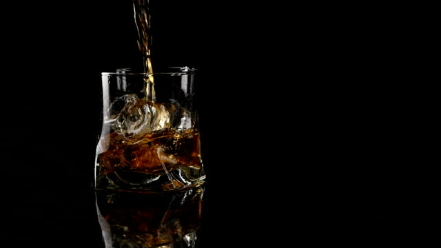 Whiskey being poured into a glass against black background. Long video