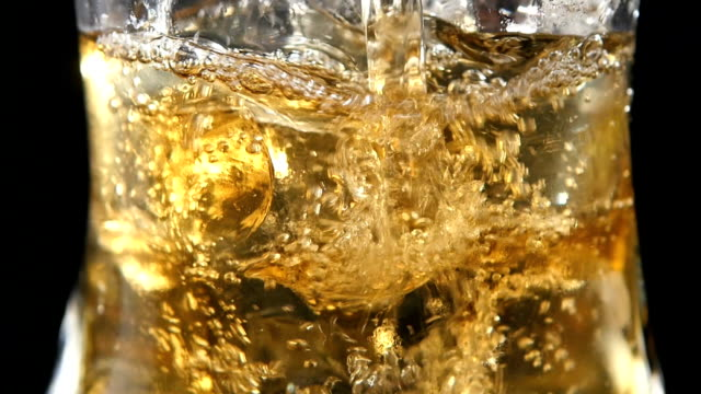 Whiskey being poured into a glass against black background. Macro. video