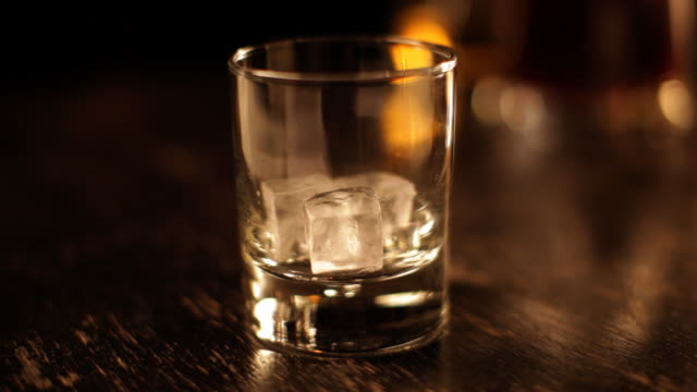 Whiskey glass filled with ice and drink, close-up video