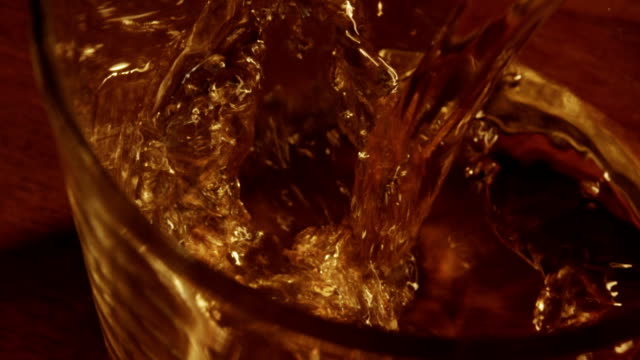 Whiskey poured into glass in slow motion video