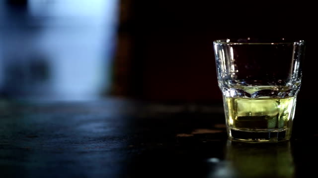 Whiskey with ice on the bar counter video