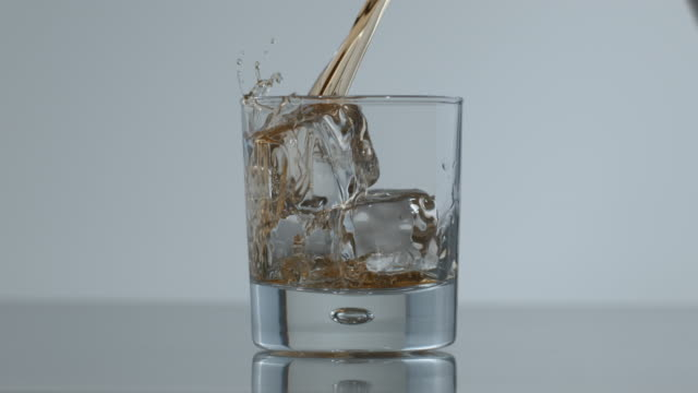 Whisky poured over ice in slow motion video