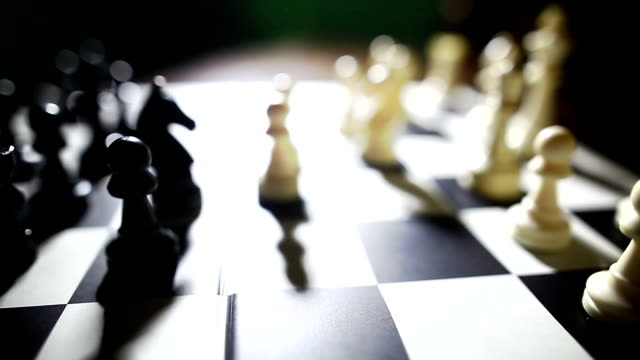 White and black pieces on a chess board with white knight moving video