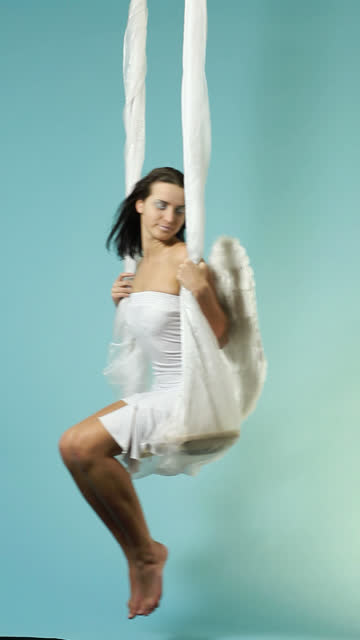 White Angel swaying on blue cloudy sky video