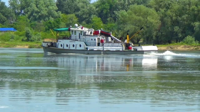 A white barge floats along the river along the shore. Cargo boat video