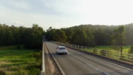 AERIAL: White car driving across road bridge in the middle of wild lush forest video
