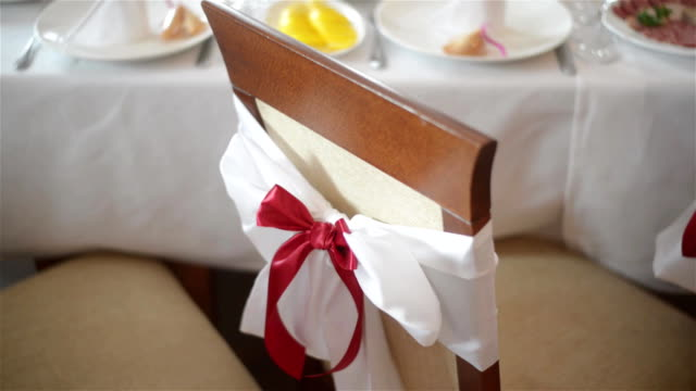 White chair with red bow close up indoors at wedding banquet or reception. Wedding decorations. The Big Day. video