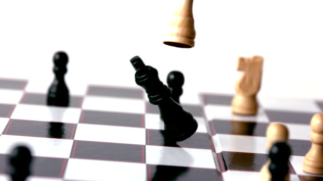 White chess piece knocking over a black one video