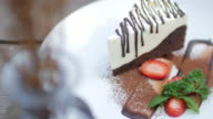 White Chocolate cake with strawberry on wooden table video
