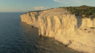 AERIAL White cliff raising above sea and shining in sunset video