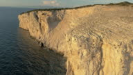 AERIAL White cliff shining in setting sun video
