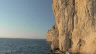 AERIAL White cliff shining in sun above sea video