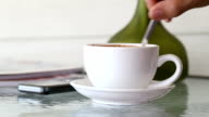 White coffee mug on glass table and hand of man stirring well and picked up to drink. video