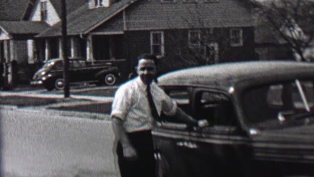 1939: White collared working man smoking pipe car owner suburban pride. video