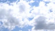 White cumulus clouds move in blue sky video