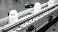 White Drug Bottles on Conveyor Moving Away video