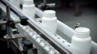 White Drug Bottles on Moving Conveyor video