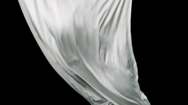 White fabric flowing on black background, Slow Motion video