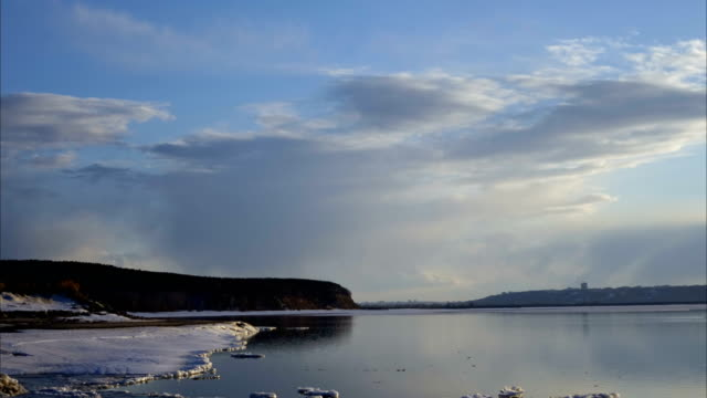 White gray clouds sail over a big lake. In the surface of the water reflected the passing clouds. Water surface start to break free from the ice. It is getting dark outside. Spring Sunny evening. Time lapse  footage. video