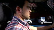 White guy driving a car sends text messages with his mobile video