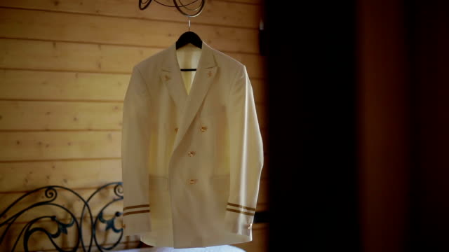 white jacket hanging from chandelier in a wooden house video