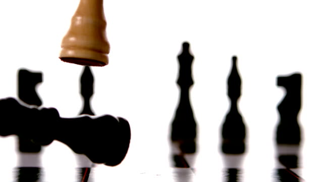 White king knocking over the black in chess video