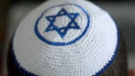 White kipah with blue Magen David on a man head, a symbol of Judaism and Zionism, close up footage from defocus to focus. video