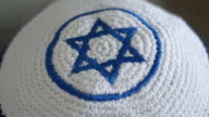 White kippah with blue Magen David on a head, a attribute of Judaism and Zionism, close up footage from defocus to focus. video