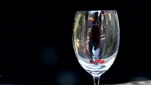 White milk pouring into cranberry fruit slow motion video