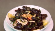 White plate with prepared mussels in wine with lemon, prawns and basil. Fresh restaurant dish. Steam video