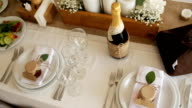White roses with greenery stand on the festive served dinner table, close-up video