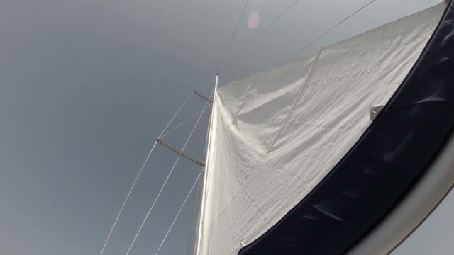 White sail in wind against sky, low angle shot, yachting video