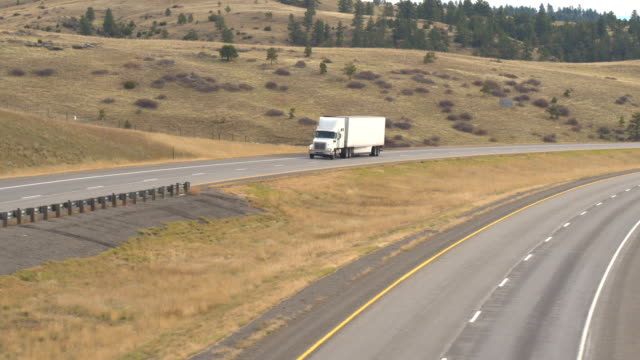 AERIAL CLOSE UP White semi truck freighting goods across the Great Plains in USA video