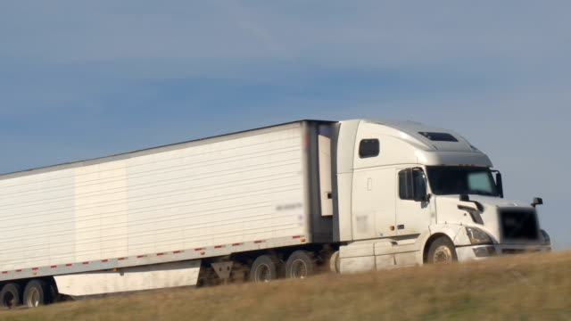CLOSE UP: White semi truck shipping goods driving along the highway on sunny day video