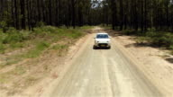 CLOSE UP: White SUV car driving along dirty road leading through lush forest video