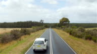 AERIAL: White SUV car driving along straight road surrounded by lush forest video