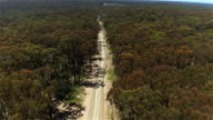 AERIAL: White SUV car driving on dusty country road in extensive vast forest video