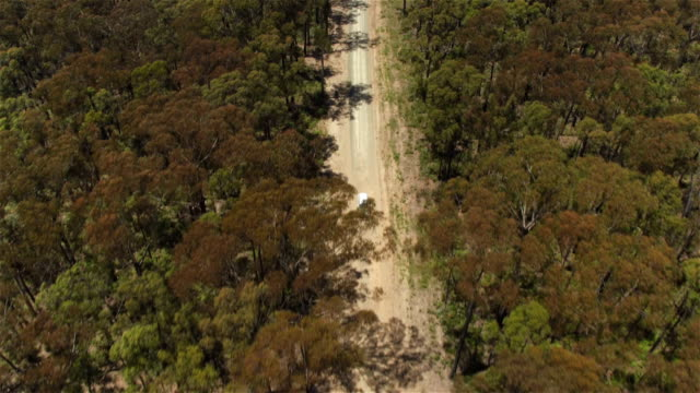AERIAL: White SUV car driving on straight dusty country road on hot sunny day video