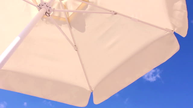 White umbrella against blue sky video