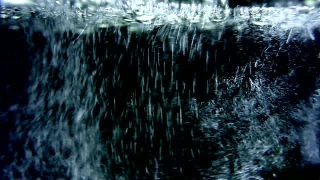 White water bubbles rise to the top on dark background video