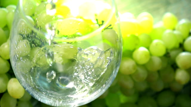 White wine being pored into a glass against bunch of green grapes. Winemaking concept. Super slow motion close up video video
