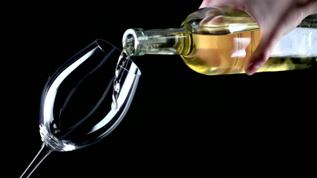 White wine being poured into a wineglass, black, closeup, slowmotion video
