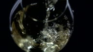 White wine being poured into a wineglass, bubble, view from above, black, closeup, slowmotion video