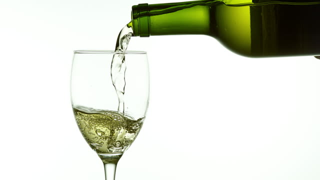 White Wine being poured into Glass, against White Background, Slow motion 4K video