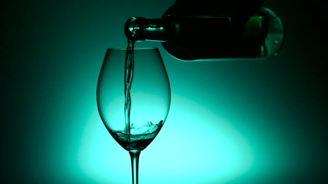 White wine beverage in crystal wineglass, green, slowmotion video