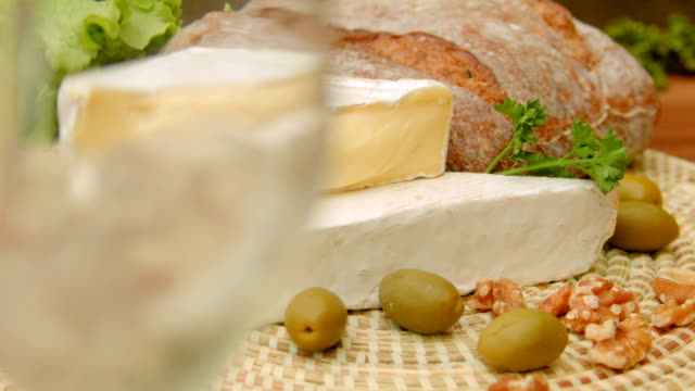 White wine is poured into a glass and brie cheese video