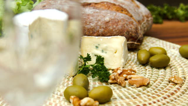 White wine is poured into a glass and Camembert cheese video