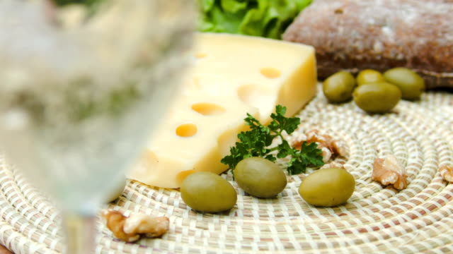 White wine is poured into a glass and Maasdam cheese video