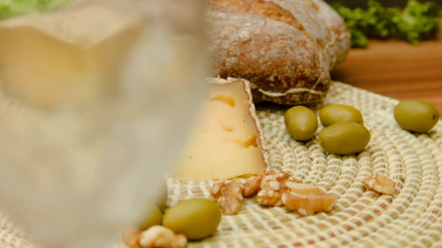 White wine is poured into a glass and tomme cheese video